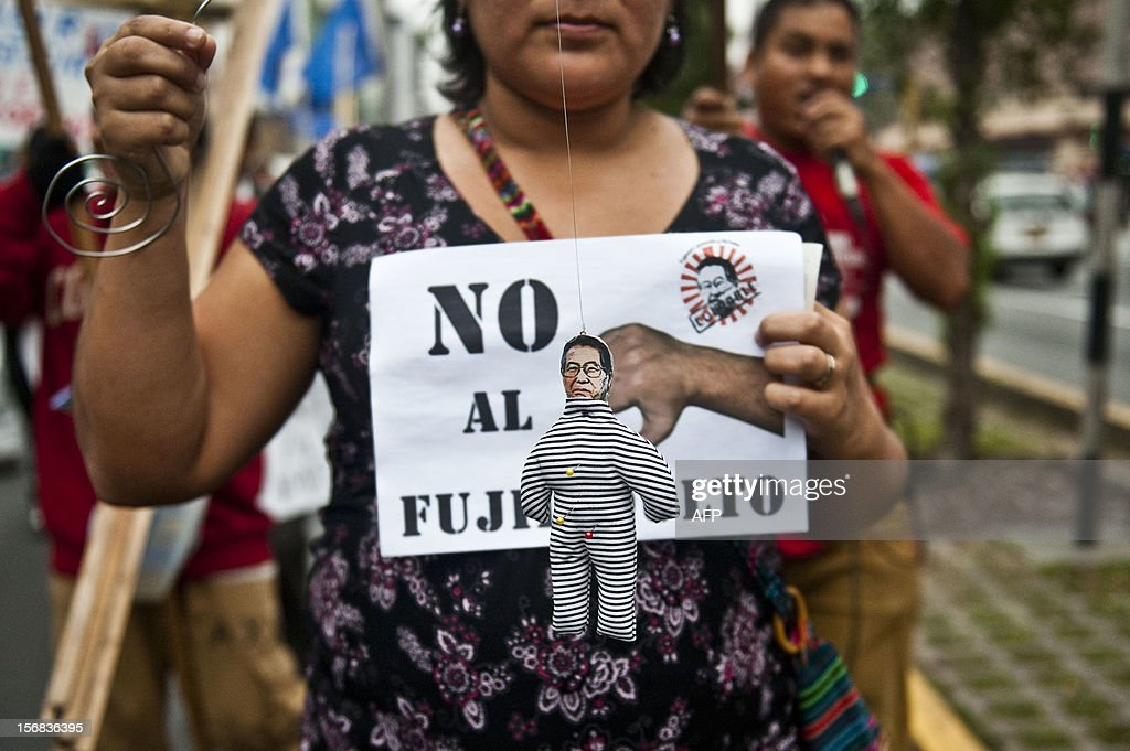 A woman holds a voodoo puppet of former Peruvian President Alberto Fujimori during a march of relatives of victims of violence, human rights activists and members of social organizations, in Lima on November 22, 2012 against the possibility of former president Alberto Fujimori --presently serving a 25-year sentence for several crimes-- being released.