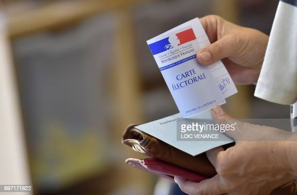 A woman holds a voting envelope and her electoral card at a polling station in Nantes western France during the second round of the French...