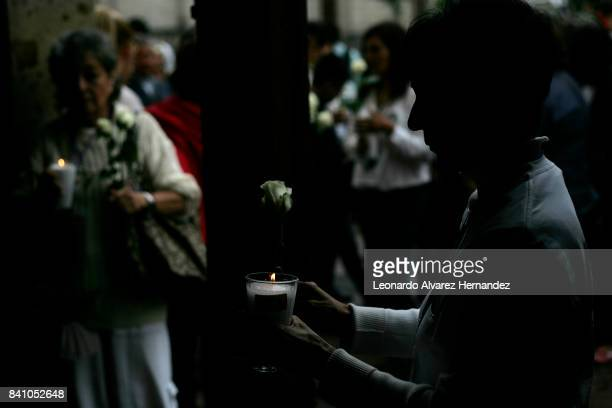 A woman holds a white candle and a rose during a protest to demand the authorities theresolution of the forced dissapearance cases as part of the...