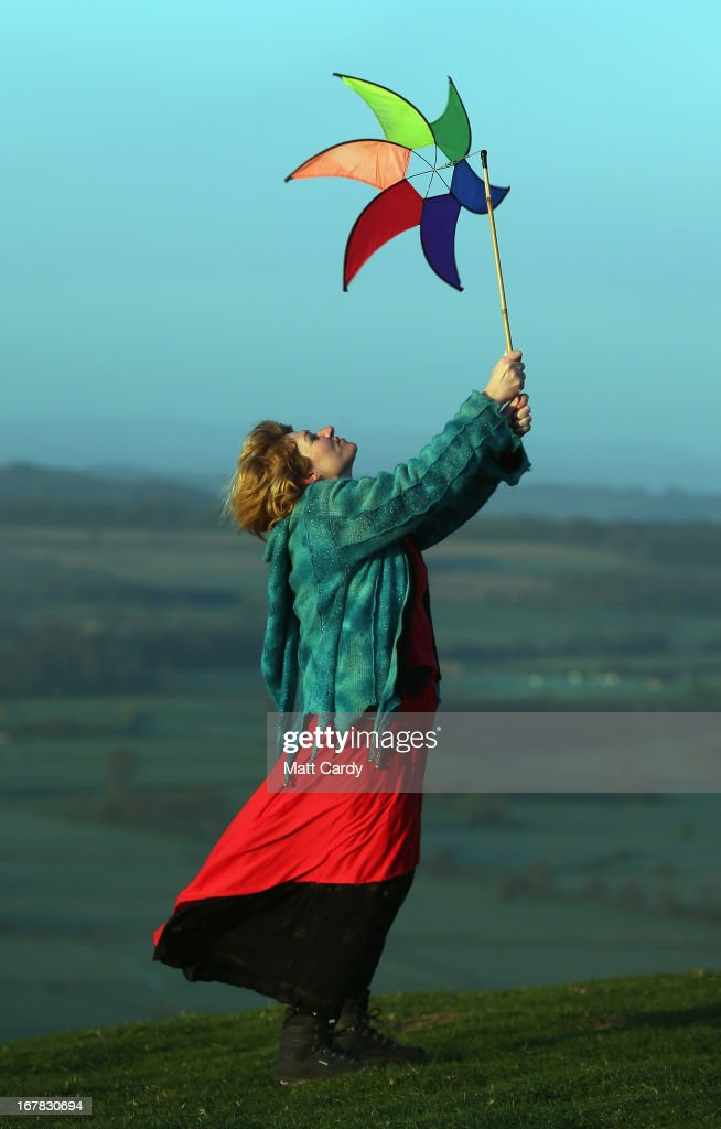 A woman holds a windmill as she watches the sun rise as they join in a Beltane dawn celebration service in front of St. Michael's Tower on Glastonbury Tor on May 1, 2013 in Glastonbury, England. Although more synonymous with International Workers' Day, or Labour Day, May Day or Beltane is celebrated by druids and pagans as the beginning of summer and the chance to celebrate the coming of the season of warmth and light. Other traditional English May Day rites and celebrations include Morris dancing and the crowning of a May Queen with celebrations involving a Maypole.