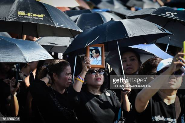 TOPSHOT A woman holds aloft an image of the late Thai King Bhumibol Adulyadej during the final dress rehearsal for his funeral in Bangkok on October...