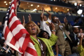 A woman holds an American flag as she cheers during day one of the Democratic National Convention at Time Warner Cable Arena on September 4 2012 in...