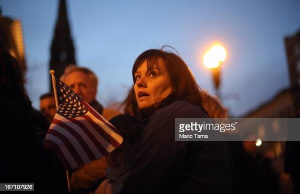 A woman holds an American flag at a makeshift memorial for victims near the site of the Boston Marathon bombings at the edge of the stillclosed...