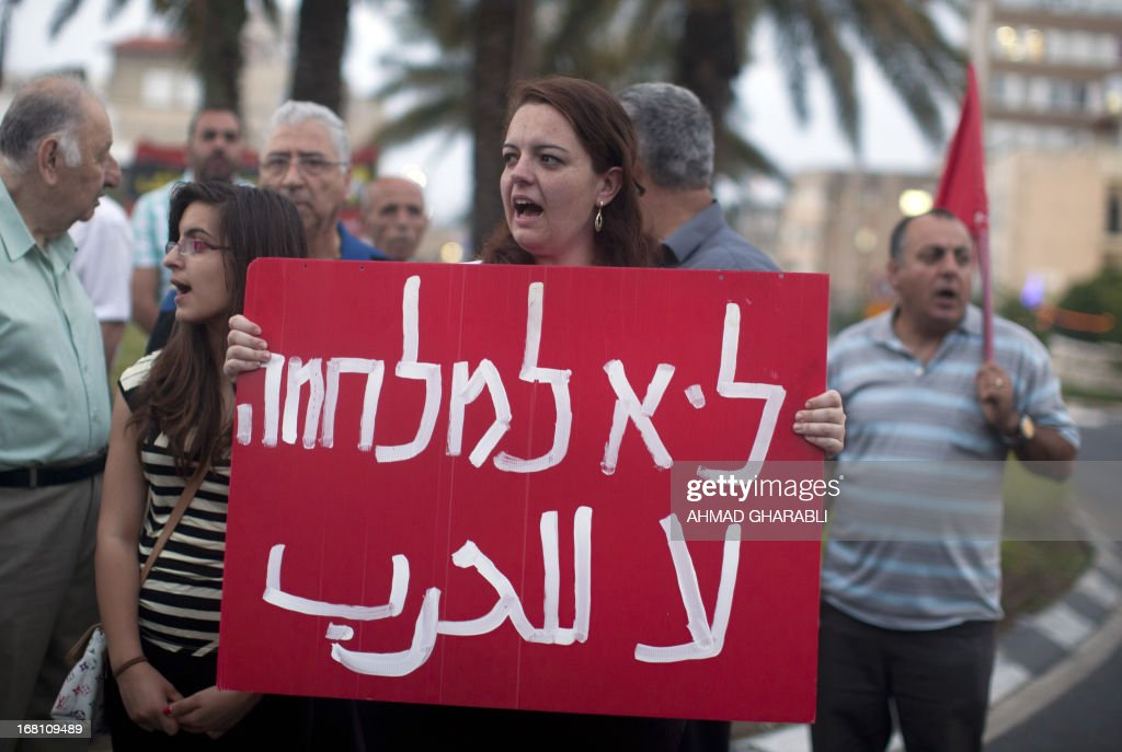 A woman holds an anti-war placard during a demonstration by Arab Israelis against the attack on Syria in the northern Israeli city of Haifa on May 5, 2013. Israel carried out a pre-dawn air strike near Damascus, targeting Iranian missiles destined for Lebanon's Hezbollah in the second such raid on Syria in three days, a senior Israeli source said. AFP PHOTO/AHMAD GHARABLI
