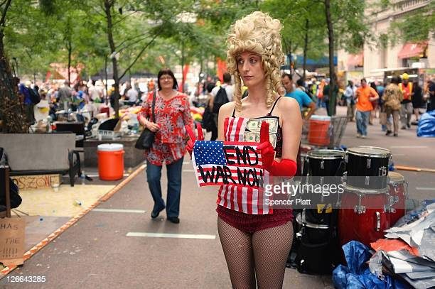 A woman holds an antiwar sign in a park where those affiliated with the 'Occupy Wall Street' demonstrations in the Financial District near Wall...