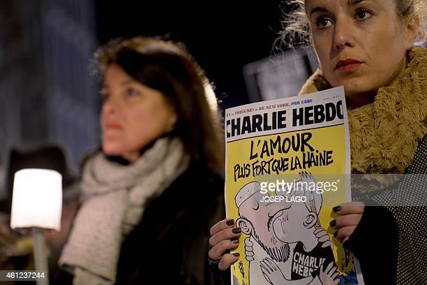 A woman holds an edition of Charlie Hebdo in front of the Consulate of France in Barcelona on January 9 2015 during a tribute for victims of a terror...