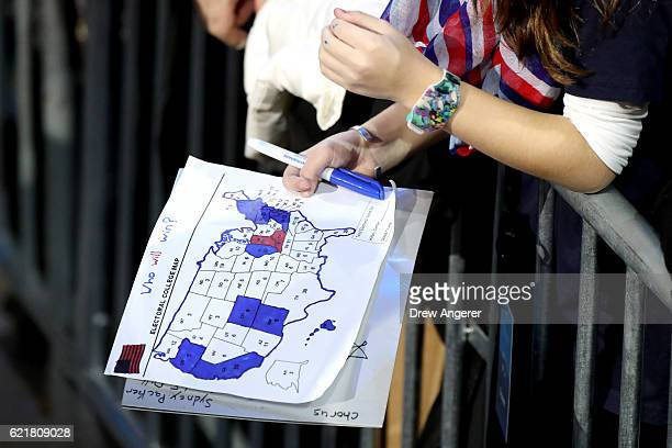 A woman holds an electoral map as voting results come in at Democratic presidential nominee former Secretary of State Hillary Clinton's election...