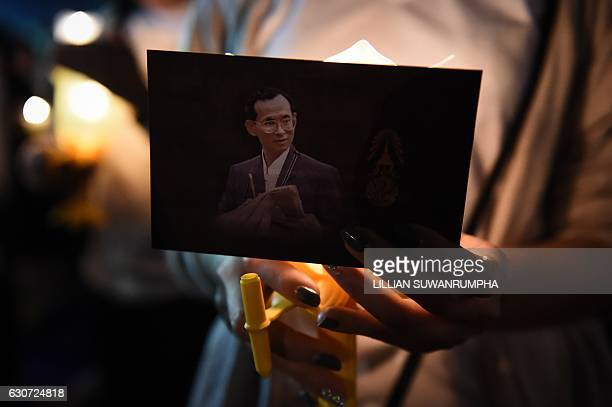 A woman holds an image of late Thai King Bhumibol Adulyadej during New Years celebrations in front of the Grand Palace in Bangkok early on January 1...