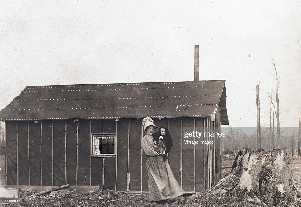 A woman holds an infant in her arms as she poses in front of a claim shack early 1910s The structure mostly walled in tar paper served to lay claim...