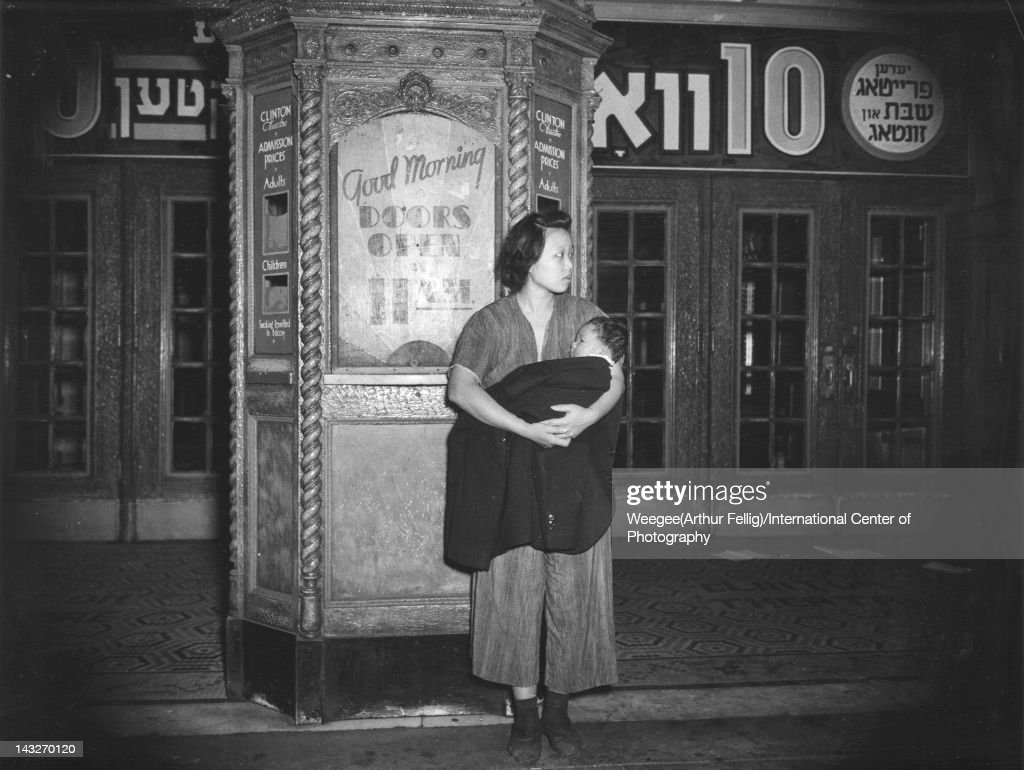 A woman holds an infant wrapped in a blanket as she stands outside a theatre following their evactuation from a fire New York New York early to mid...