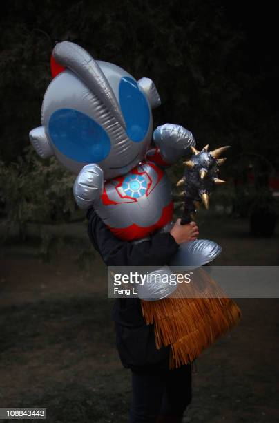 A woman holds an Ultramanlike character doll at the Ditan temple fair for celebrating the Lunar New Year of Rabbit on February 5 2011 in Beijing...
