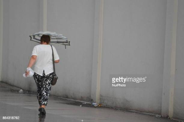 A woman holds an umbrella as she walks on a raindrenched road during a rainy autumn day in Ankara Turkey on September 26 2017 The temperature in...