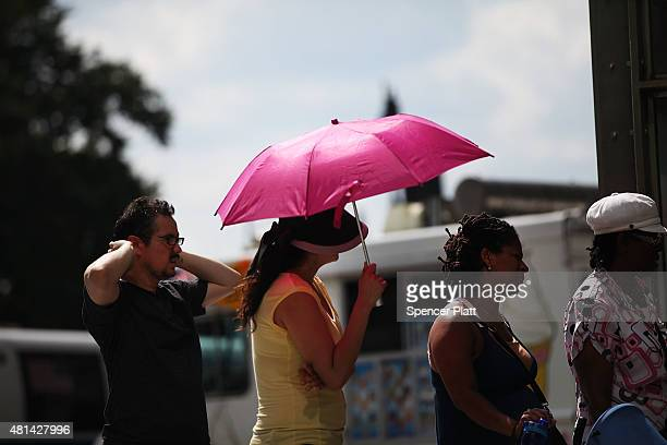 A woman holds an umbrella on a Manhattan street on one of the hottest days of the summer on July 20 2015 in New York City More than 20000 homes and...