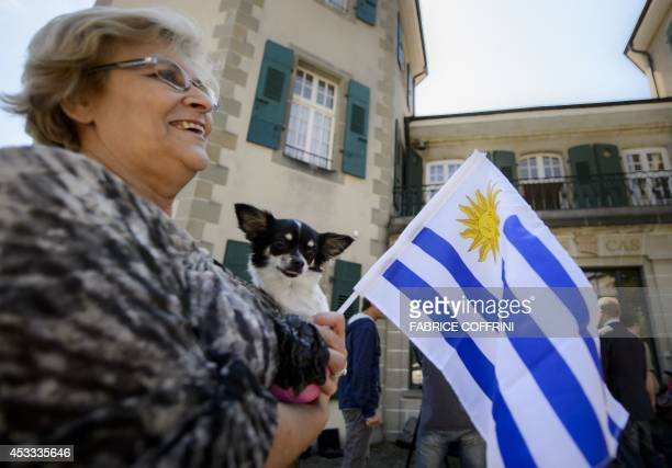 A woman holds an Uruguayan flag and a dog in front of the Court of Arbitration for Sport on August 8 2014 in Lausanne Uruguayan forward Luis Suarez...