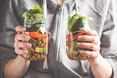 A woman holds and eats salad in a glass jar with baked chickpeas, guacamole and vegetables. Healthy diet detox vegan food concept.