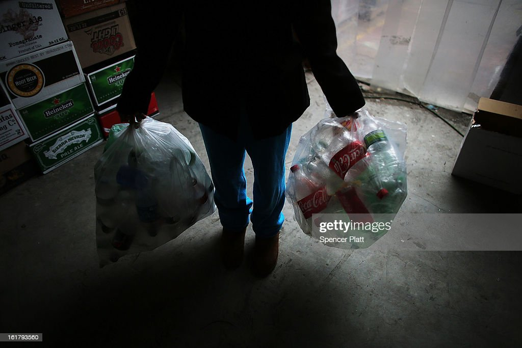 A woman holds bags of empty bottles to be sorted at Sure We Can, a non-profit bottle redemption center in Bushwick, Brooklyn that is pushing to become a cooperative for the canning community on February 16, 2013 in New York City. Sure We Can, which was partly started by homeless canners in 2007 and is run by one of its founders Sister Ana Martinez de Luco, looks to give the diverse members of the canning community a safe and fraternal place to redeem cans, store their carriages and become members of an association that encourages self-dependence and responsibility. Many of New York's canners are non-English-speaking elderly immigrants who live a marginalized existence and are vulnerable to dishonest business practices. Sure We Can currently serves around 50 canners per day and recycles over 6 million bottles and cans per year.