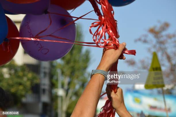 A woman holds balloons as people protest against the Turkish government's new education policies in Ankara Turkey on September 16 2017 The Turkish...