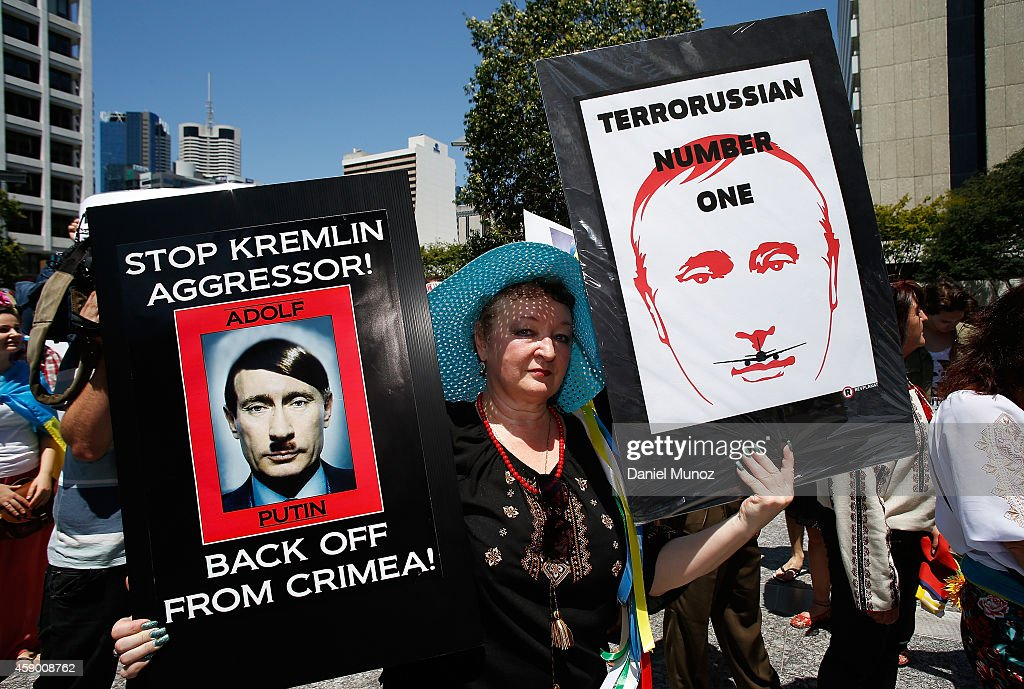 A woman holds banners against Russian President Vladimir Putin during a protest against G20 leaders on November 15, 2014 in Brisbane, Australia. World leaders have gathered in Brisbane for the annual G20 Summit and are expected to discuss economic growth, free trade and climate change as well as pressing issues including the situation in Ukraine and the Ebola crisis.