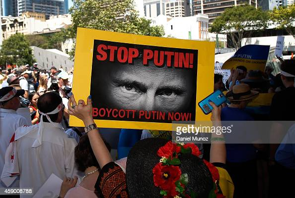 A woman holds banners against Russian President Vladimir Putin during a protest against G20 leaders on November 15 2014 in Brisbane Australia World...