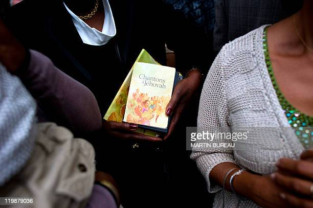 A woman holds books of prayer as she attends a Jehovah's Witnesses assembly gathering 30000 believers on July 23 2011 in Villepinte Paris suburb...