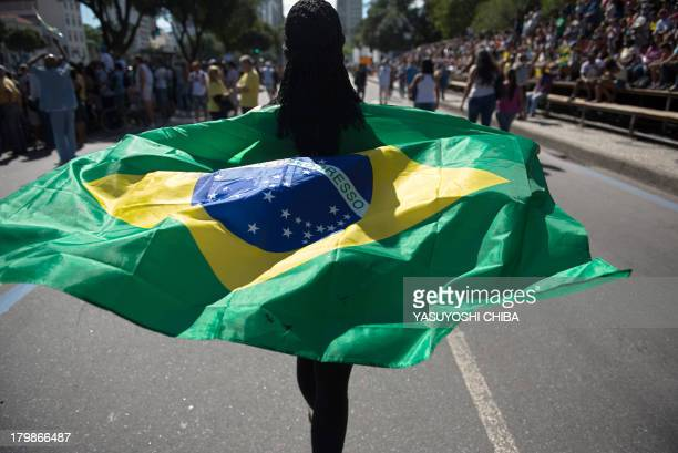A woman holds Brazil's national flag during the Independence day parade in Rio de Janeiro Brazil on September 7 2013 A series of demonstrations...