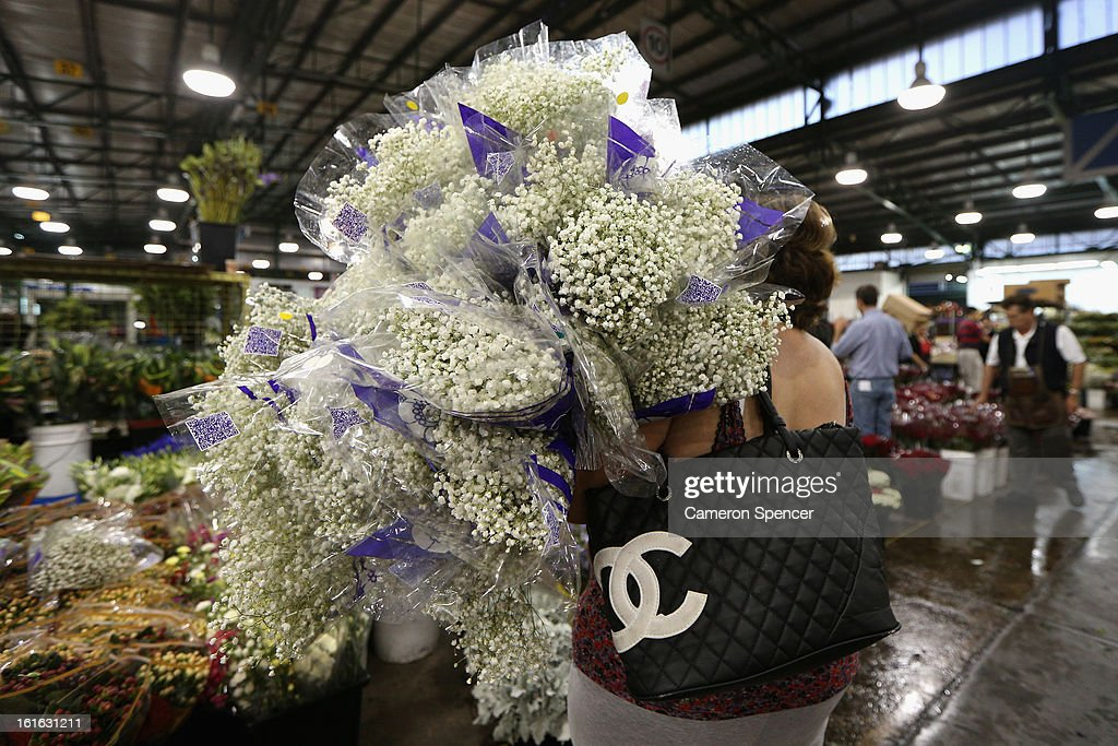 A woman holds bunches of flowers on Valentines Day at Sydney Flower Market on February 14, 2013 in Sydney, Australia. Due to an unusually hot January in Australia an increasing number of roses have been sourced from South America and Africa to ensure Valentines supplies don't run out.