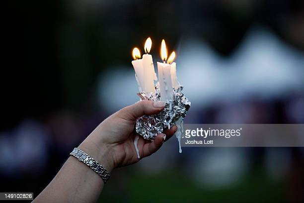 A woman holds candles during a memorial service outside the Aurora Municipal Center July 22 2012 in Aurora Colorado The memorial was for the victims...