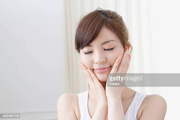 Woman holds cheeks by hand