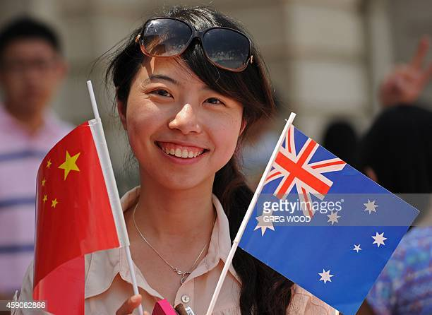 A woman holds Chinese and Australian national flags as she waits to catch a glimpse of China's President Xi Jinping as he drives by during the G20...