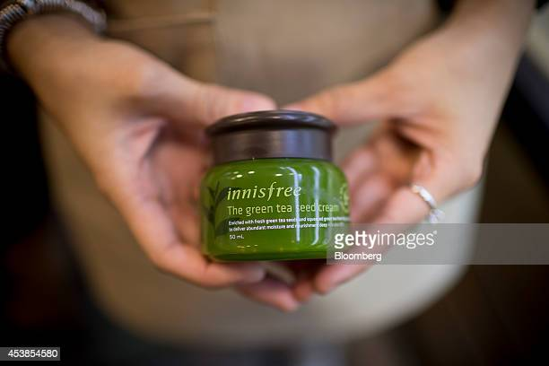 A woman holds container of green tea seed cream in an arranged photograph at Amorepacific Corp's Innisfree store in the Causeway Bay district of Hong...