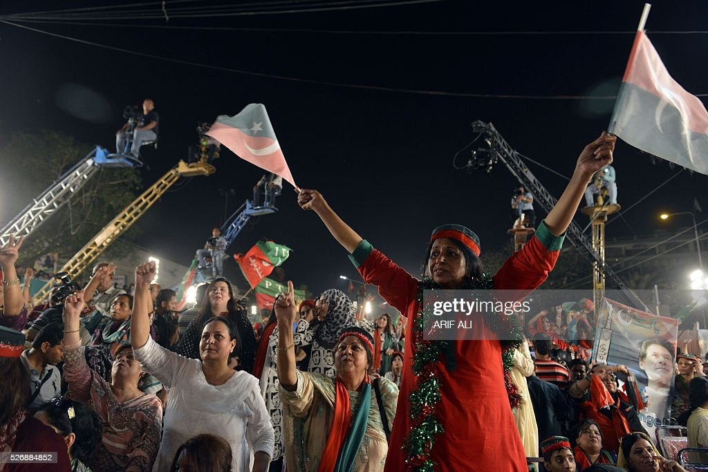 A woman holds flags of opposition party Pakistan Tehreek-e-Insaf (PTI) as she attends an anti-government rally in Lahore on May 1, 2016, on the Panama Leaks issue. Pakistan's Prime Minister Nawaz Sharif pledged on April 22, 2016 to resign if a probe related to the Panama Papers tax scandal found his family had committed any wrongdoing. Three of Sharif's children were named in a vast leak of documents from Panama-based law firm Mossack Fonseca this month that has revealed how the wealthy hide their money. ALI