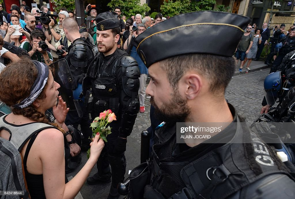 A woman holds flowers in front of French gendarmes during a protest against the government's controversial labour reforms near the Place de la...
