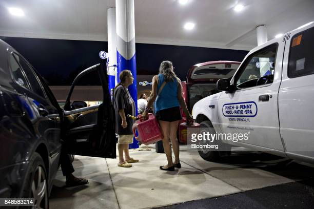 A woman holds fuel cans while attempting to negotiate with a police officer unseen as he announces the gas station is closing due to a county wide...