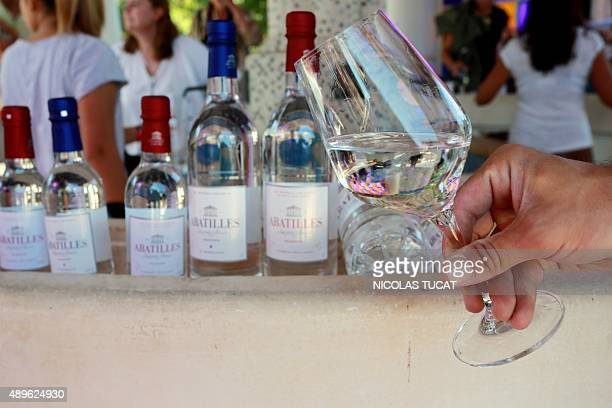 A woman holds glass of wine filled with mineral water source 'Les Abatilles' in Arcachon during a tasting session on August 25 2015 Since 2013 Jean...