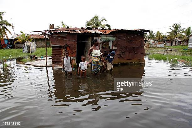 A woman holds hands with her children as they stand in front of their flooded home after torrential rains in Monrovia on July 8 2013 AFP PHOTO / STR