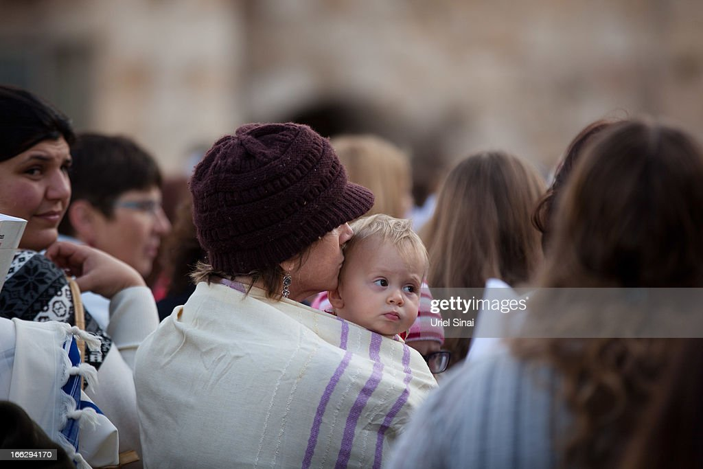 A woman holds her baby as member of the religious group 'Women of the Wall' pray at the Western Wall on April 11, 2013 in Jerusalem's Old City, Israel. Five members of the organisation 'Women of the Wall' were detained by police during the group's monthly prayer at the Western Wall, after covering themselves with prayer shawls in contradiction to the holy site's custom.