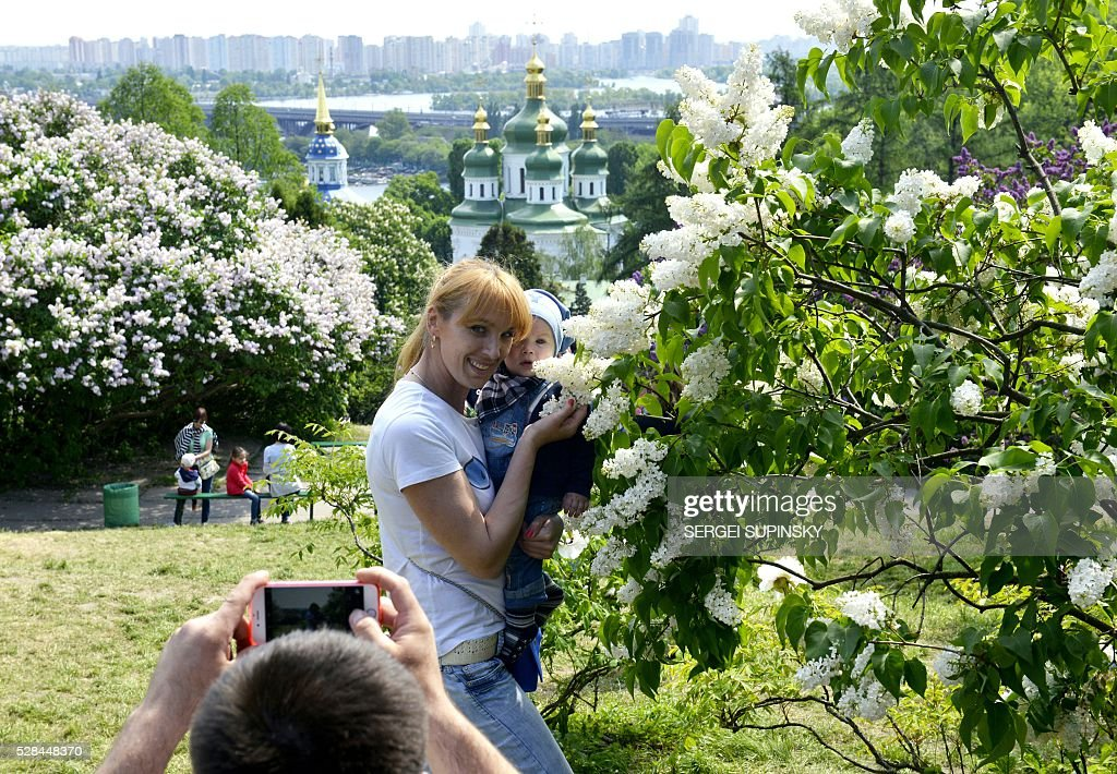 A woman holds her baby as she poses for a photograph among blossoming lilac in the Botanical Garden in Kiev on May 5, 2016. / AFP / Sergei SUPINSKY