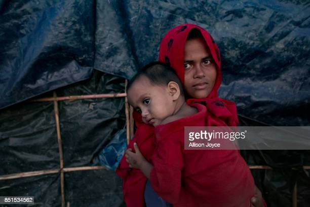 COX'S BAZAR BANGLADESH SEPTEMBER 21 A woman holds her baby in Unchiprang camp on September 21 2017 in Cox's Bazar Bangladesh Over 230000 child...