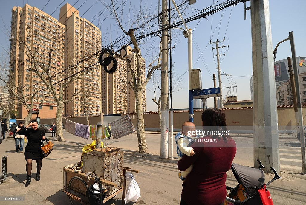 A woman holds her baby on a street in front of residential blocks in Shanghai on March 6, 2013. Chinese couples are flocking to divorce to evade a new tax on home sales after the government cracked down on property speculation, the Shanghai Daily newspaper reported on March 6. AFP PHOTO / Peter PARKS