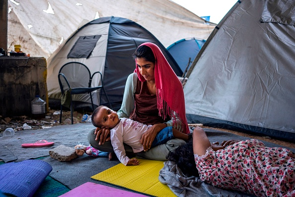TOPSHOT - A woman holds her baby on her arms as she sits on the ground among tents at the port of Piraeus, where nearly 1,500 refugees and migrants live at a makeshift camp or in passenger areas, i...
