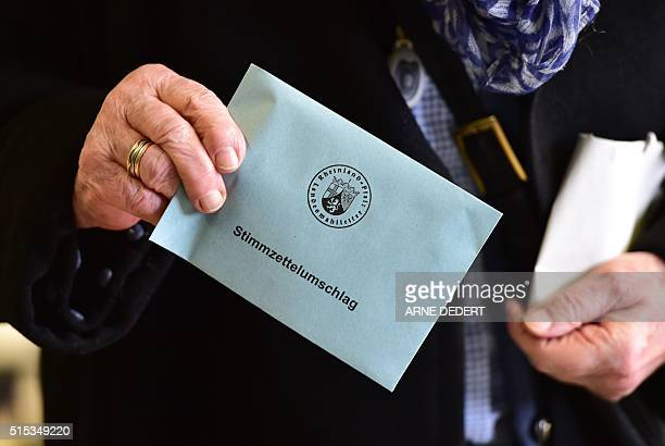 A woman holds her ballot at a polling station in Bad Kreuznach southern Germany on March 13 2016 More than 12 million voters head to the ballot box...