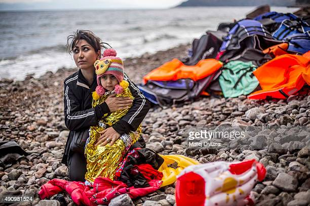 A woman holds her child as she arrived with other refugees on the shores of the Greek island of Lesbos after crossing the Aegean sea from Turkey on...