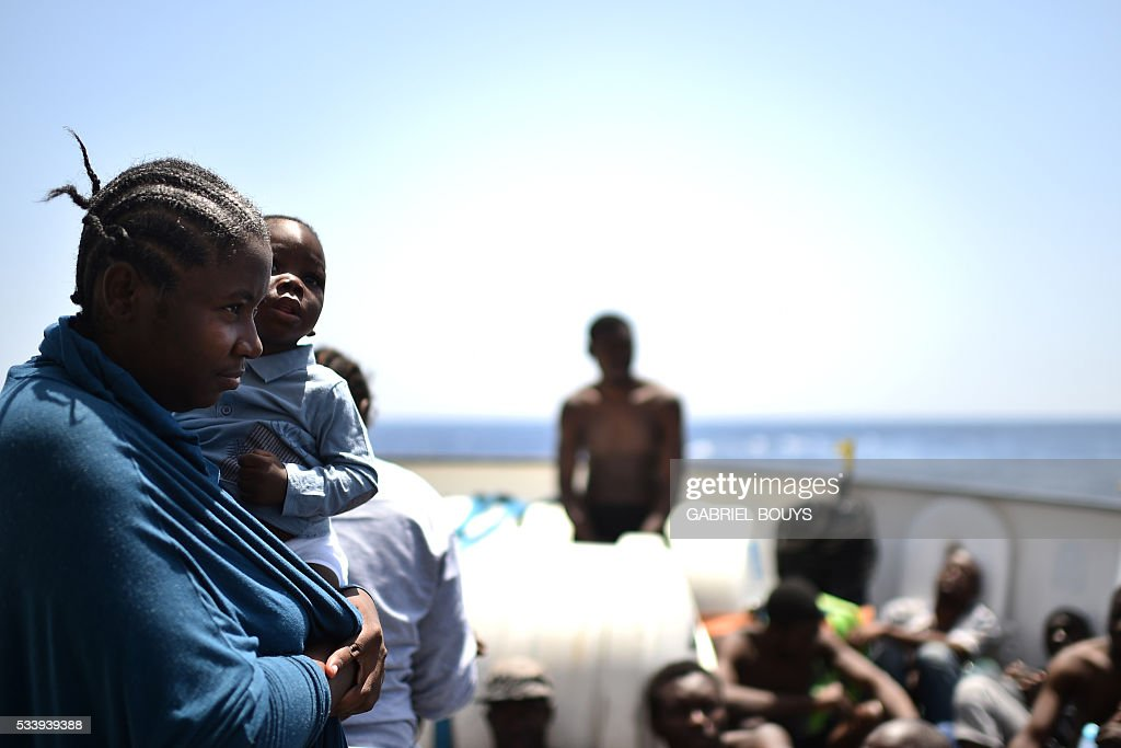 A woman holds her child during a rescue operation at sea of migrants and refugees with the Aquarius, a former North Atlantic fisheries protection ship now used by humanitarians SOS Mediterranee and Medecins Sans Frontieres (Doctors without Borders), on May 24, 2016 in the Mediterranean sea in front of the Libyan coast. / AFP / GABRIEL