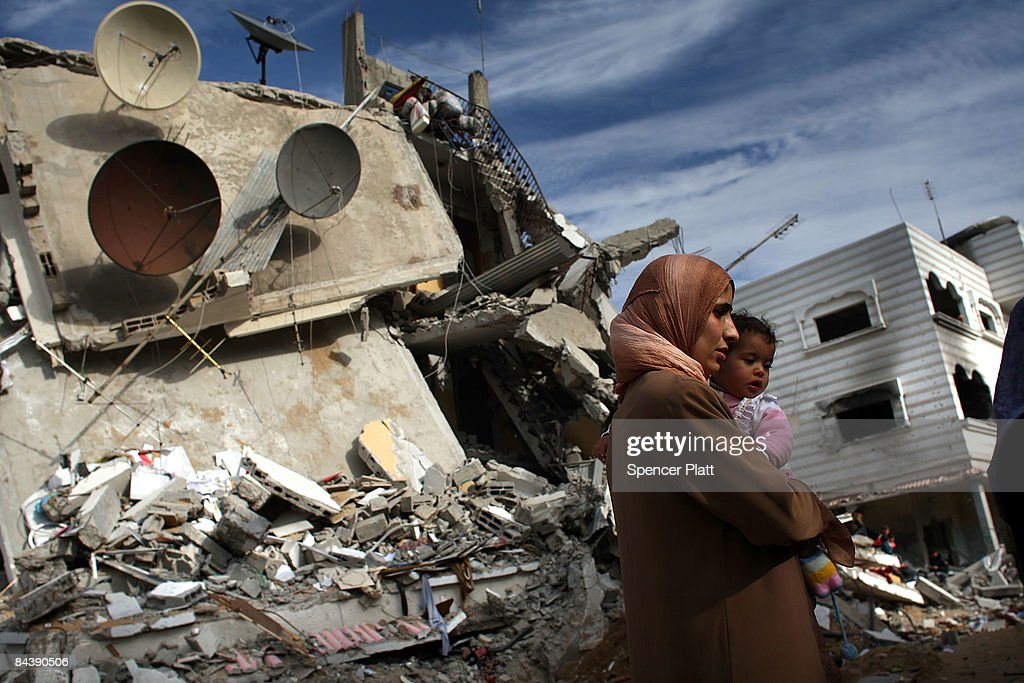 A woman holds her child in front of a demolished buildingJ anuary 21 2009 in a suburb of Gaza City Gaza Strip Over 70 percent of Gaza is still...