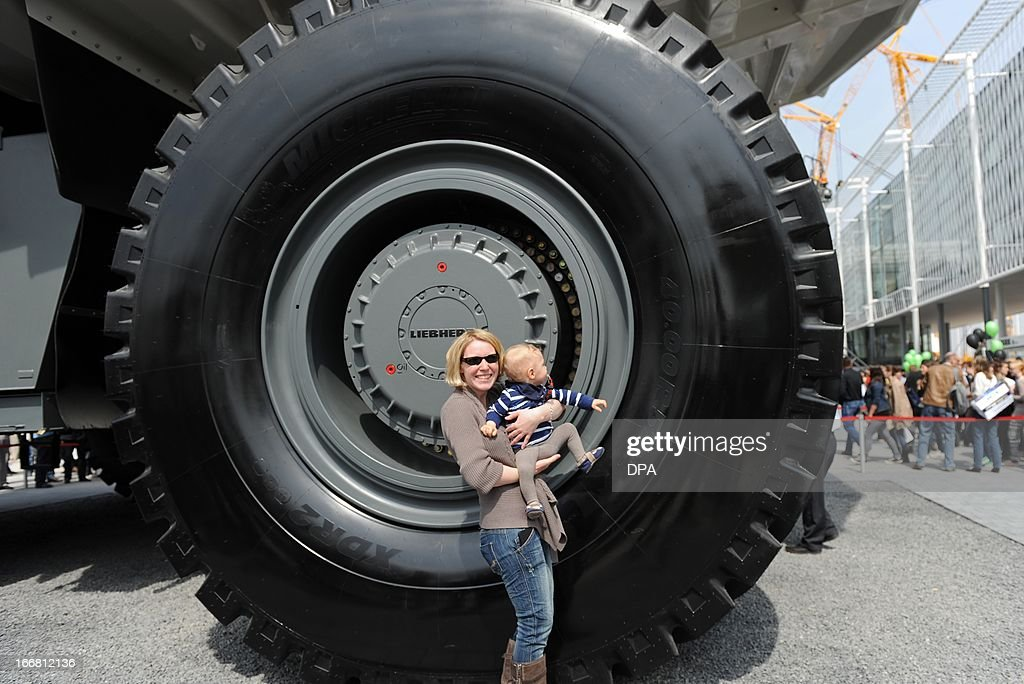 A woman holds her child in front of a wheel of a dumper at the construction machine trade fair 'Bauma' in Munich southern Germany on April 17 2013...