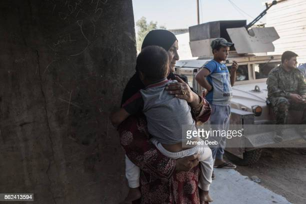 A woman holds her child next to fighters as she returns to her house after the USbacked Syrian Democratic Forces liberated some neighbourhoods in the...