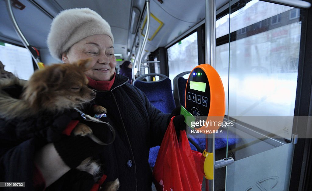 A woman holds her dog while she holds a green special card to a reading device in a bus in Tallinn, on January 9, 2013. From January 1, 2013, residents of the Estonian capital can use public transports in Tallinn for free after purchasing a special card for 2 euros.