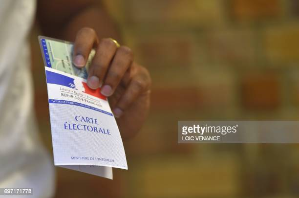 TOPSHOT A woman holds her electoral card at a polling station in Nantes western France during the second round of the French parliamentary elections...
