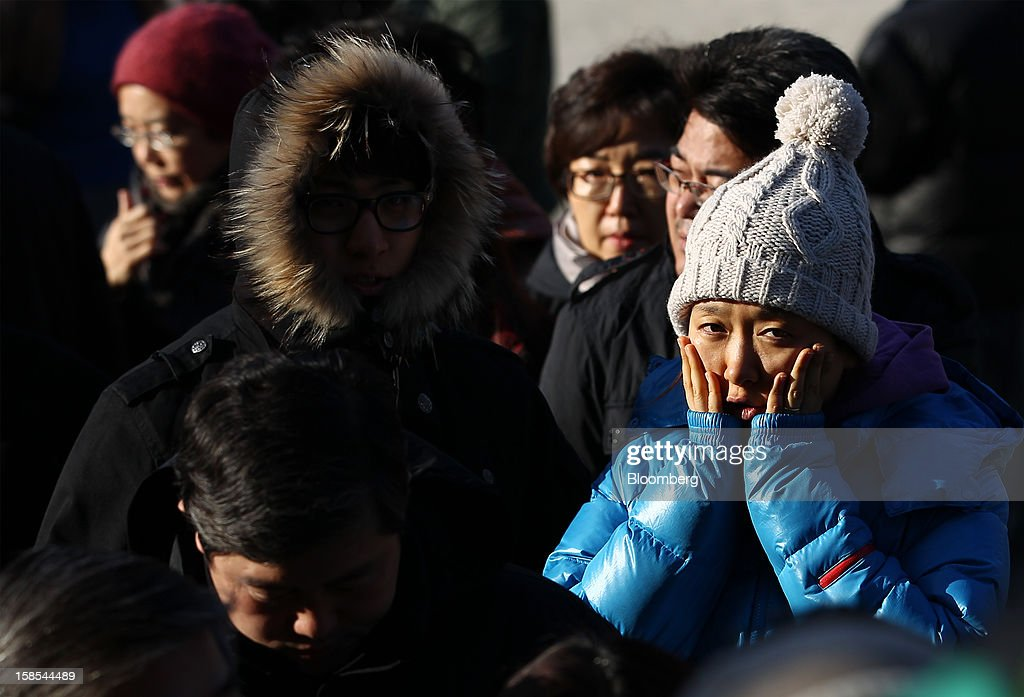 A woman holds her face in cold weather as she waits in line to cast her ballot for the presidential election at a polling station in Seoul, South Korea, on Wednesday, Dec. 19, 2012. South Koreans go to the polls today to choose either a dictator's daughter or a one-time dissident as president, both of whom pledge to reverse slowing growth, a widening income gap and deteriorating North Korea ties. Photographer: SeongJoon Cho/Bloomberg via Getty Images