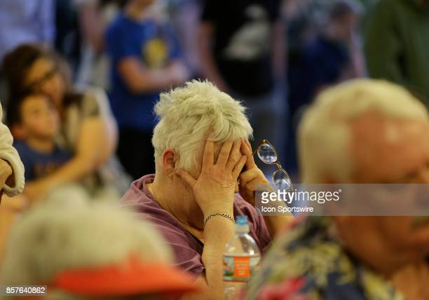 A woman holds her head during a prayer vigil held at Mountain Crest Park for the victims of Sunday night's shooting on October 3 2017 in Las Vegas...
